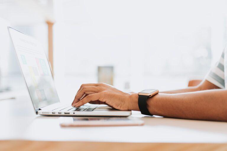 Person working on sleek laptop wearing smartwatch