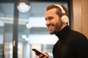 man wearing white over the ear headphones listening to phone