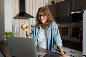 woman video chatting with glass of wine