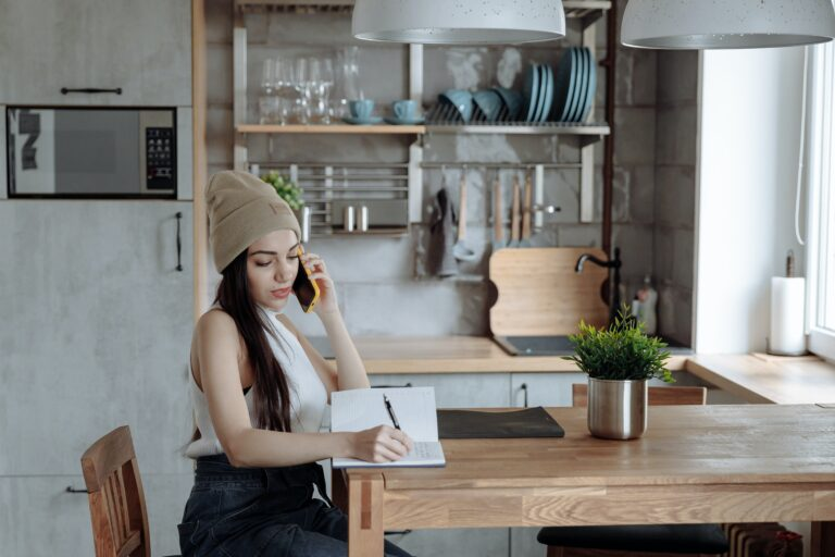 woman in a beanie on the phone writing in her notebook.