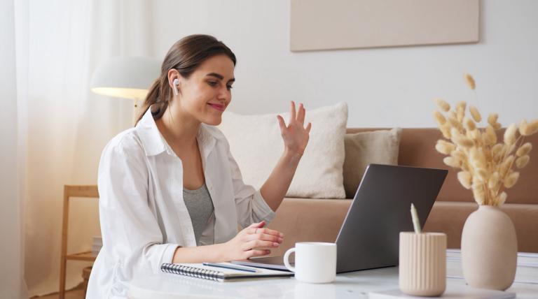 woman smiling and waving to her laptop.