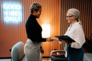 a woman shaking hands interviewing another woman for a job.