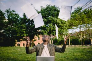 man throwing resumes into the air