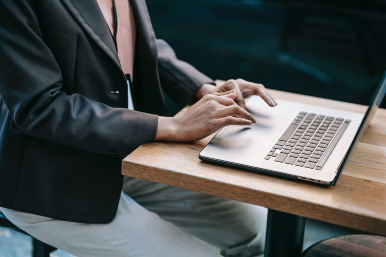 a woman in a suit jacket typing on her computer