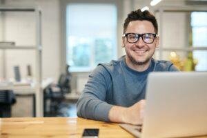 man with black glasses smiling while on his computer.