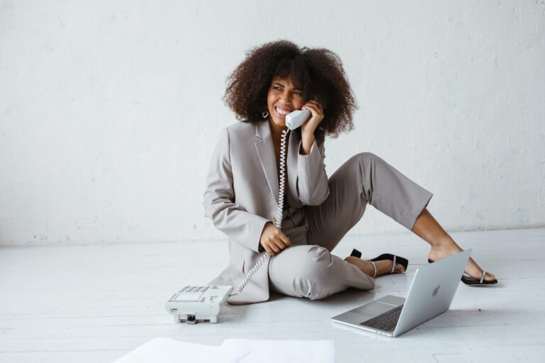 a woman in a gray suit sitting on the floor on her computer.