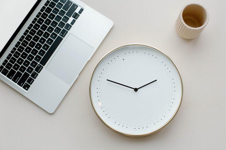 a clock sitting on a desk with a coffee mug