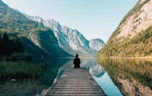The man sitting on a dock in a valley on a lake.