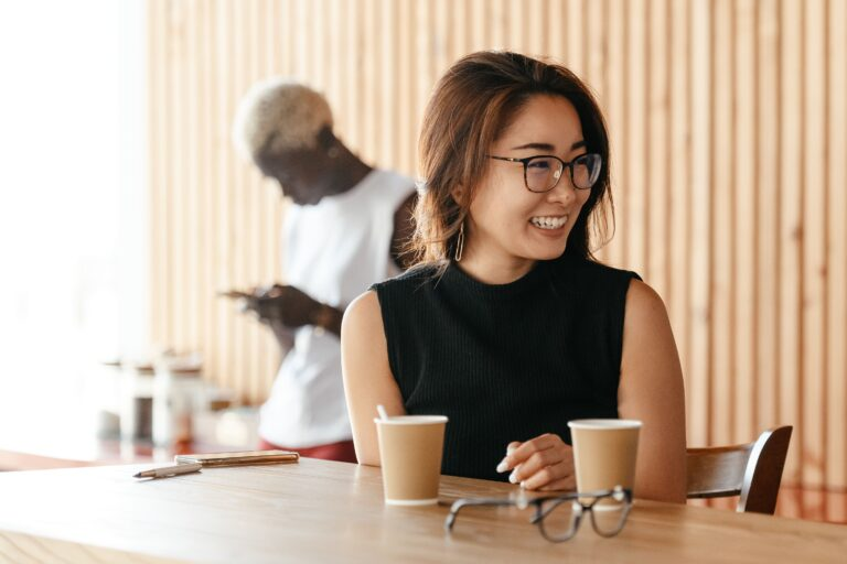 an asian woman smiling while drinking coffee in the office.