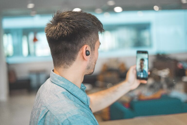 A guy recording a video of himself on his phone while he is wearing earbuds.