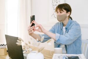 a woman in the office wearing a mask while working and facetiming.