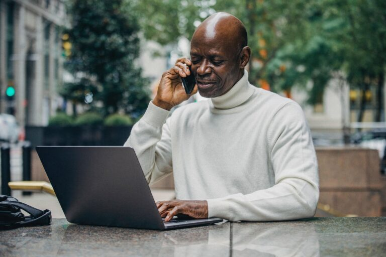 a black man in a white turtleneck on the phone and on his computer.