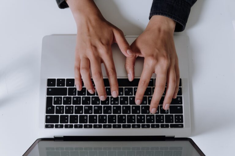 a man typing on his macbook computer