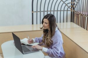 a woman in a purple sweater taking notes and on her computer.