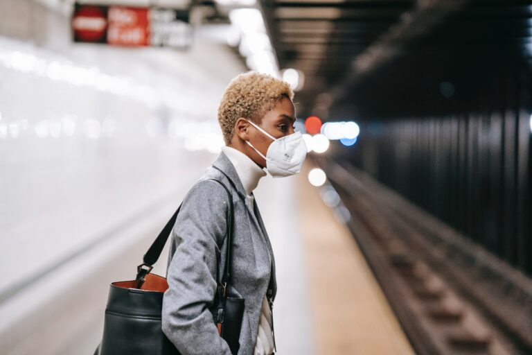 a black woman wearing a mask in professional clothing waiting for the subway.