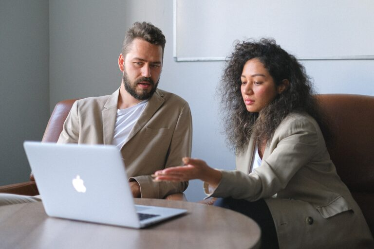 a man and a woman working together on a macbook.